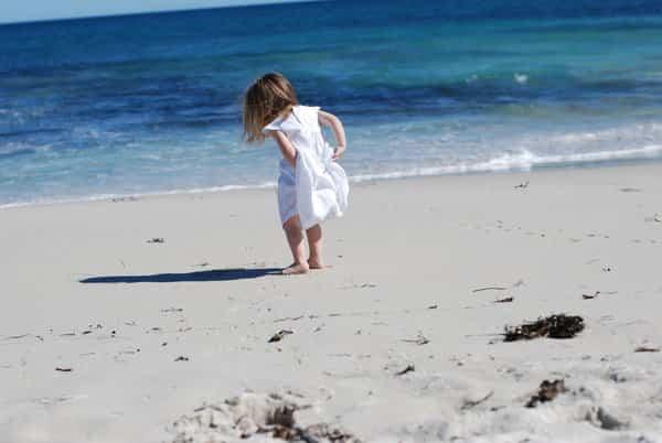 niña con vestido blanco en la playa