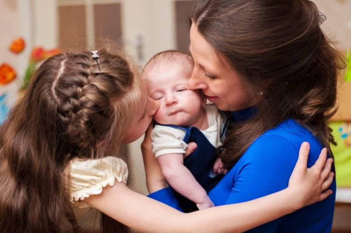 depositphotos 46076525 stock photo mom hugs baby and older