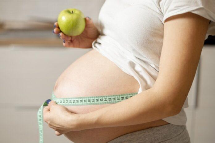 vista lateral mujer manos sosteniendo manzana midiendo su vientre 23 2148352150