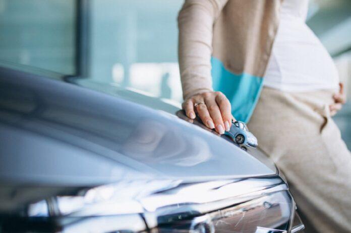 mujer embarazada joven que elige coche sala exposicion automoviles 1303 21059