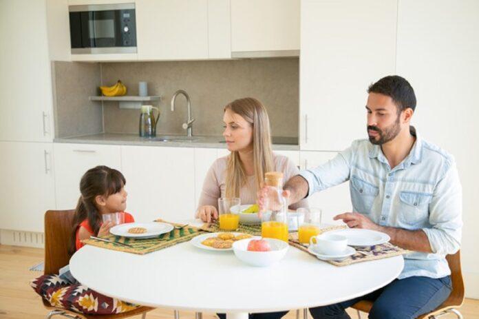 pareja padres nina desayunando sentados mesa comedor frutas galletas jugo naranja hablando comiendo 74855 8159