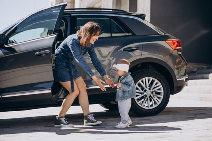 madre su bebe divirtiendose junto al coche aparcado cerca su casa 1303 27846